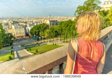 Close up of elegant caucasian woman looking skyline of Paris from Sacred Heart viewpoint. Parisian views from terrace of Sacre Coeur Cathedral, the highest city point of Paris, France. Sunny day.