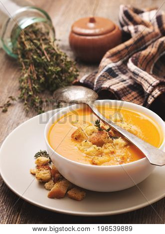 pumpkin soup - puree with croutons in a white bowl on the old wooden background