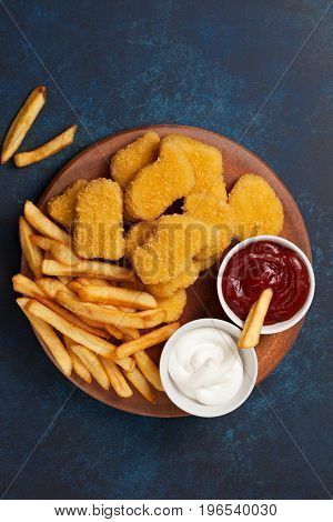 Chicken nuggets and french fries sauces of ketchup and mayonnaise on a blue background. view from above