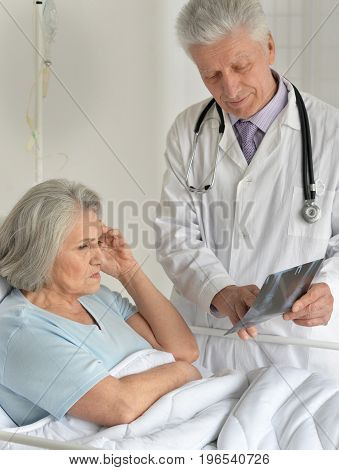 senior doctor showing radiograph to senior female patient in the hospital