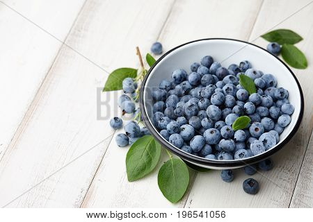 Fresh ripe blueberries with leaves in bowl on white wooden planks