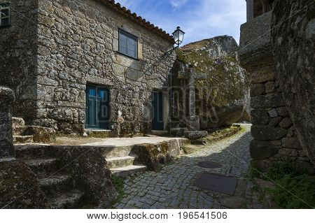 Narrow cobblestone street between bolders and houses in the historic village of Monsanto in Portugal; Concept for travel in Portugal