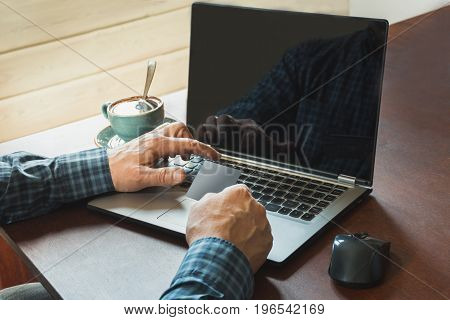 Side view shot of a man's hands holding card and using laptop sitting at wooden table with cup of coffee. Close up.