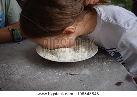 Child plays fetch a prize in a bowl of flour