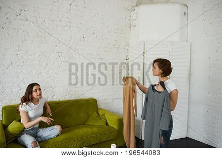 Two girls getting dressed before going for a walk or party: woman holding dresses and her friend on couch helping her to choose between them. People clothing style fashion and shopping concept