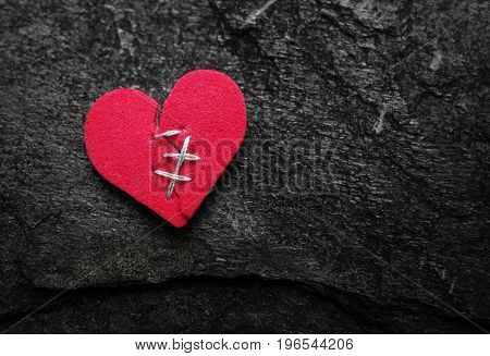 Broken red heart with stitches on textured background