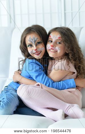 Portrait of cute little girls with faces painted
