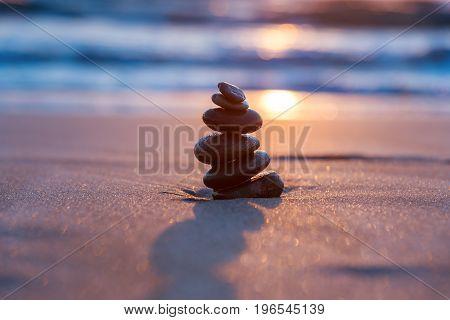 Stones Balance in sunrise at sea in summer