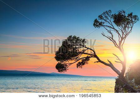 Amazing sunset landscape with rocky island and colorful sky Brela Makarska riviera Dalmatia Croatia Europe