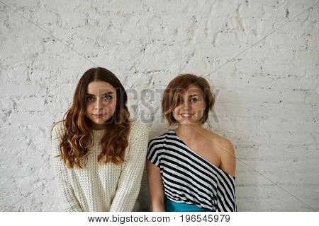 Indoor fashion portrait of two charming young women best friends wearing stylish clothes and natural make-up posing for picture against white brick wall background with copy space for your text