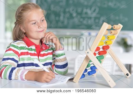 Little girl sitting at table and learning to use abacus