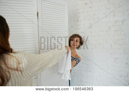 Two girls shopping together: unrecognizable woman giving white dress to attractive young female who is trying on new clothes in fitting-room or cabin. Shopping style fashion and consumerism concept