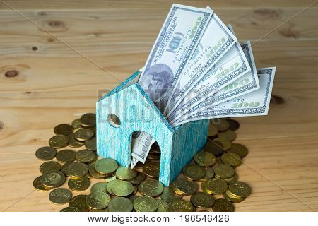 Conceptual Image Of Small House With Gold Coins And Hundred Dollar Bills On Wooden Surface. Selectiv