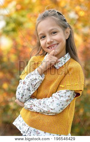Portrait of cute little girl smiling in autumnal park