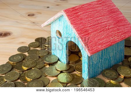 Conceptual Image Of Small House With Gold Coins On Wooden Surface. Selective Focus.