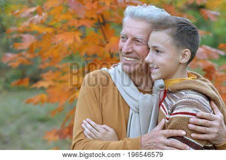 happy grandfather and grandson hugging  in park