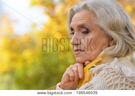 Senior beautiful  sad woman with leaf posing outdoors
