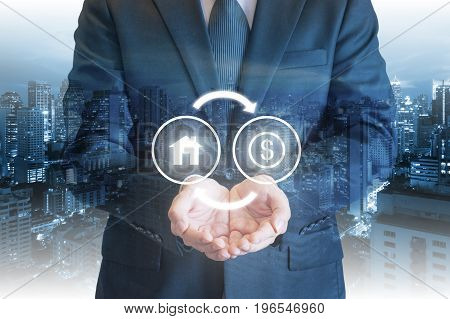 Business Man Holding Out Hands Under House And Money Exchanging Icons With Cityscape Background For