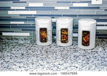Three White Pasta Canisters On Marble Counter Top