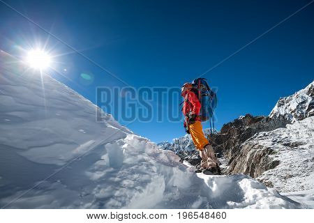 Trekker looks at the sun while crossing Cho La pass in Everest region Nepal