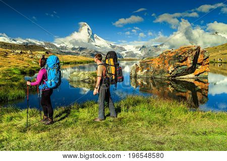 Young couple walking with backpack and camping equipment on the mountain trail near Stellisee lake Valais region Zermatt Switzerland Europe