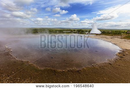 Large eruption of the biggest active geysir or geyser Strokkur with tourists waiting around, Golden circle, Iceland. Hot spring with steam in front of the geyser.