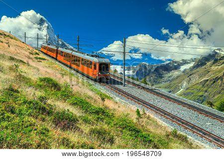 Famous electric red tourist train coming down from the Gornergrat station in Zermatt touristic resort Valais region Switzerland Europe