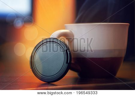 Lens cap against the background of a cup of tea the equipment of a photographer
