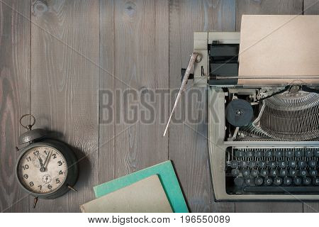 An old typewriter with paper an alarm clock and notepads lie on a table