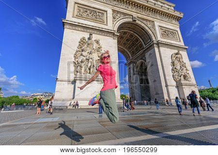 Carefree woman jumping at Arch of triumph. Caucasian lifestyle traveler enjoys at Arc de Triomphe, a popular landmark in Paris, France. Weekend in European Capitals. Freedom and travel concept.