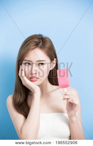 woman take popsicle and feel upset with sensitive problem on the blue bakcground