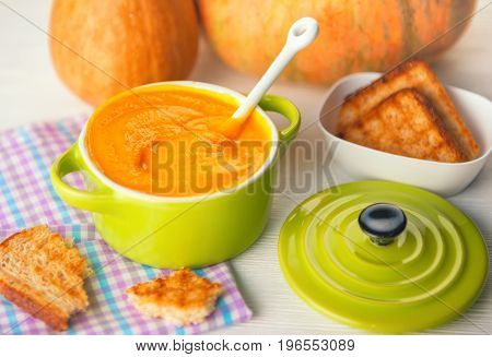 Still Life Of Creamy Pumpkin Soup And Bread In Green Bowl On Napkin