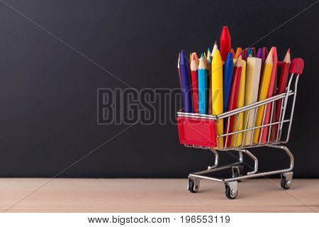 Education Concept With Chrome Shopping Cart, Pens, Crayons, Colorful Chalks On Black Chalkboard Back