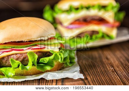 Two Homemade Full Cheeseburgers With Vegetables, Spices And Beef Meat On Dark Wooden Background, Clo