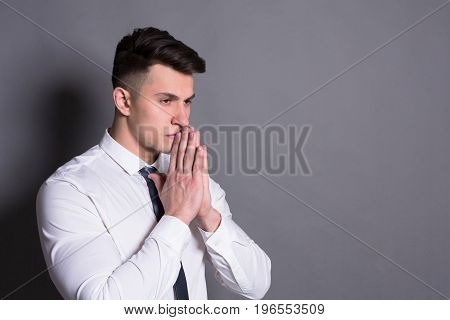 Successful businessman. Pensive young man standing at gray studio background, copy space