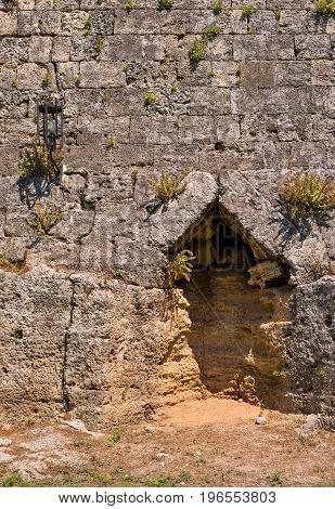 big stone wall of ancient fortress with a niche