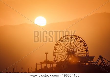 Sunset behind Santa Monica pier with ferris wheel