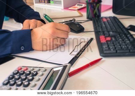 People calculate about and note data cost at home Finance managers taskConcept business and finance. Man hand with pen calculator and computer on wooden table - color / Old Polaroid
