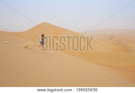 Woman Running In Rub Al Khali Desert At The Empty Quarter, In Abu Dhabi, Uae