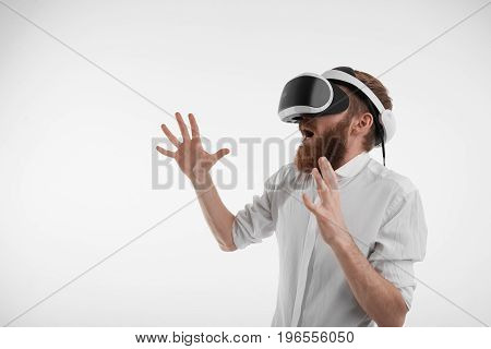 Profile picture of young bearded manager in formal shirt wearing virtual reality goggles entertaining himself during break at office exclaiming and gesturing as if interacting with someone