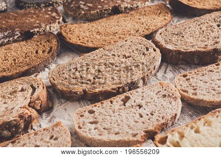 Sliced sorts of bread gradient background. Bakery and grocery concept. Fresh, healthy whole grain sliced sorts of rye and white loaves on wood