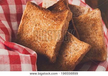 Breakfast background, white bread toasts on checkered table napkin, closeup