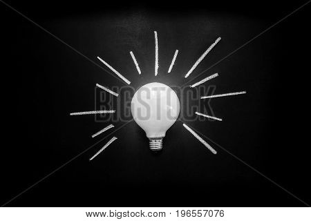 Light bulb with rays written by white chalk on the black chalkboard light bulb idea business idea business concept Innovation concept
