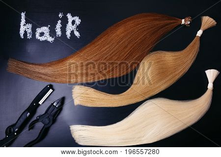 Set of of three colors hair extension tools on a dark background