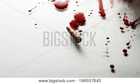 Bullet and red blood on a white