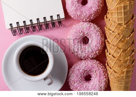 Tasty fresh pink glazed donuts with ice cream waffle cones coffee and notebook on pink background. Top View. Concept Sweet Morning Food Life.