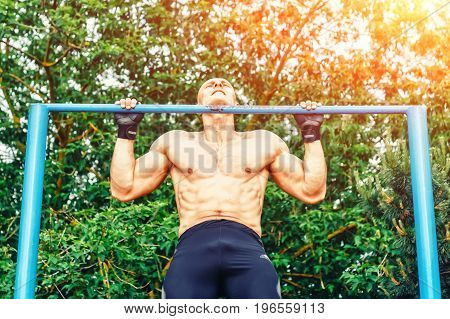 Closeup of strong bald athlete doing pull-up on horizontal bar.