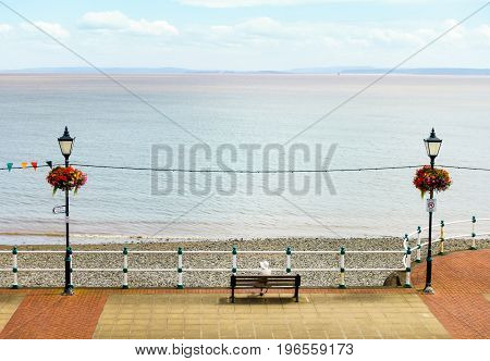 Aerial view of a elderly woman sitting on a bench on the esplanade in Penarth looking at the sea.