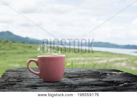 Hot drink in a cup on grunge wood and nature blurred background