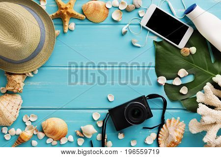 Vacation background on blue wood, top view with copy space. Beach accessories, photo camera and seashells